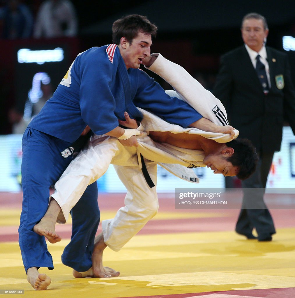 Korea's Hong Suk Woong (white) fights against Austria's Marcel Ott (blue) on February 10, 2013 in Paris, during the eliminatories of the Men - 81kg of the Paris Judo Grand Slam tournament. AFP PHOTO
