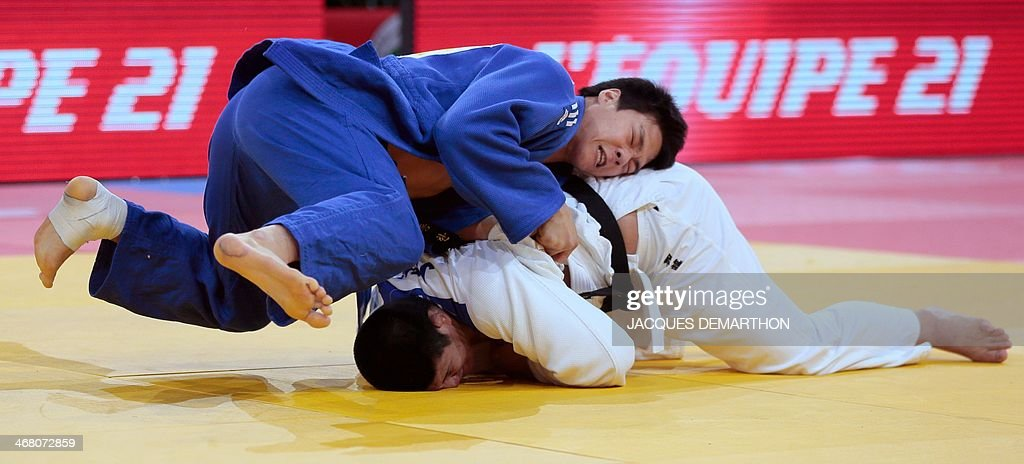 Korea's Kwak DongHan pins down Japan's Kato Hirotaka during the men's 90kg repechage fight at the 2014 Paris Judo Grand Slam tournament on February 9...