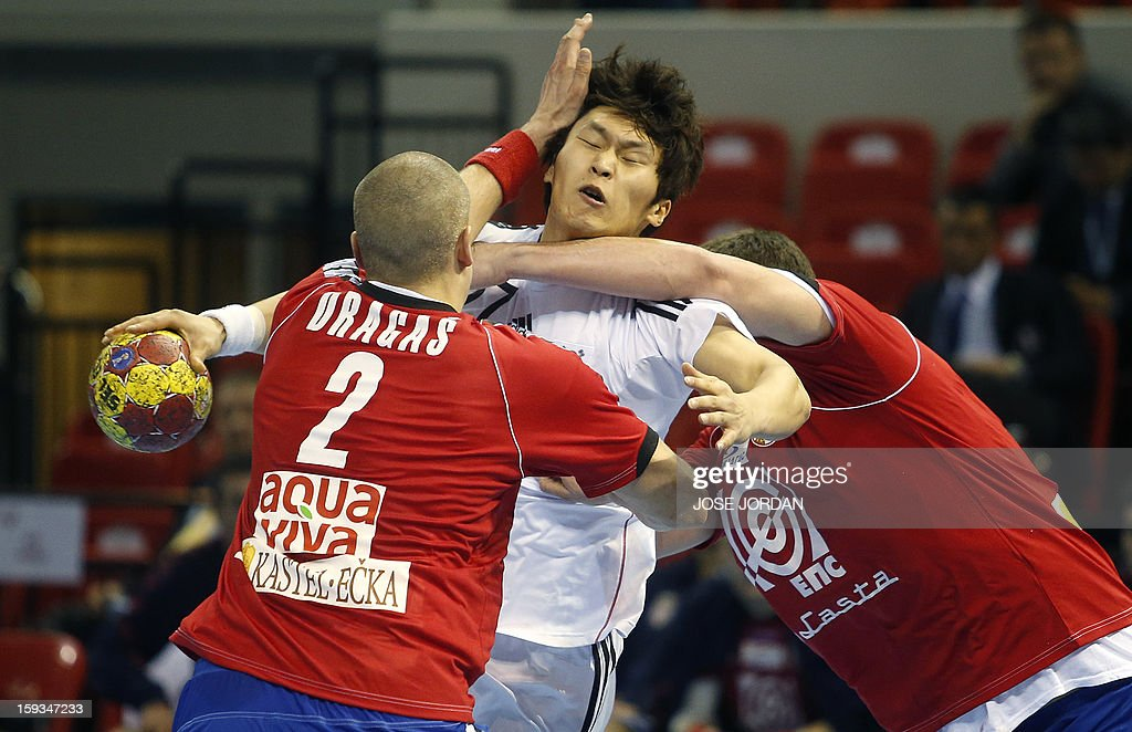 Korea's wing Han Jeong (C) vies with Serbia's back Milos Dragas (L) and Serbia's back Mijajlo Marsenic during the 23rd Men's Handball World Championships preliminary round Group C match Serbia vs Korea at the Pabellon Principe Felipe in Zaragoza on January 12, 2013. AFP PHOTO / JOSE JORDAN