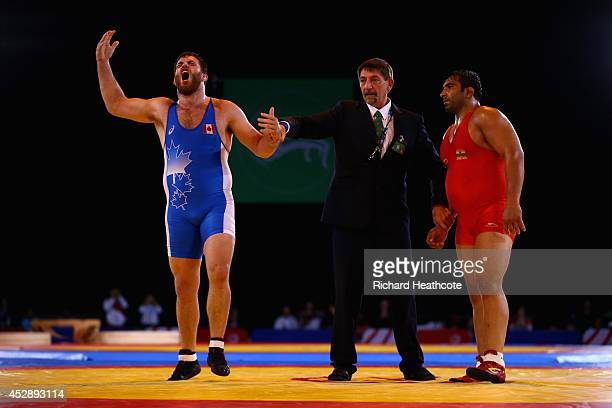 Korey Jarvis of Canada celebrates beating Rajeev Tomar of India in the 125kg Freestyle Wrestling Gold medal match at Scottish Exhibition And...