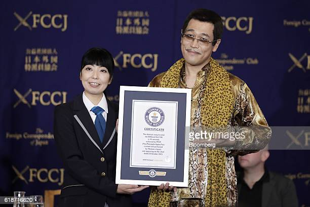Kosaka Daimaou also known as singer Pikotaro right poses for a photograph as he receives a Guinness World Records Ltd certificate during a news...
