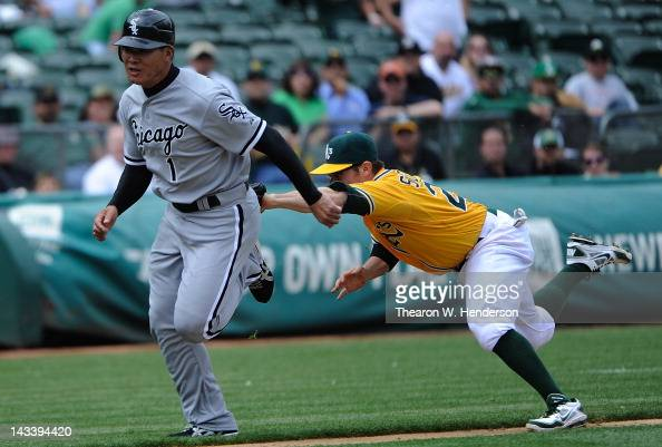 Koskuke Fukudome of the Chicago White Sox get caught in a rundown and is tagged out by Eric Sogard of the Oakland Athletics in the seventh inning at...