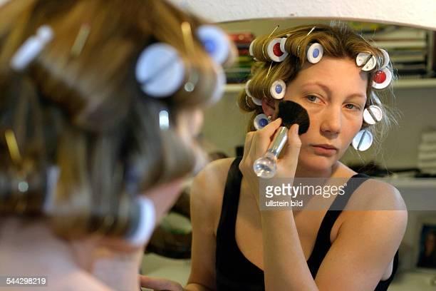 Kosmetik Schönheitspflege Frau mit Lockenwicklern im Haar vom Spiegel pudert sich die Wangen