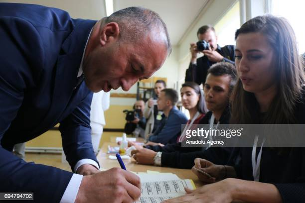 Kosovan Prime Minister candidate Ramush Haradinaj signs after casting his vote at a polling station during a snap parliamentary contest after the...