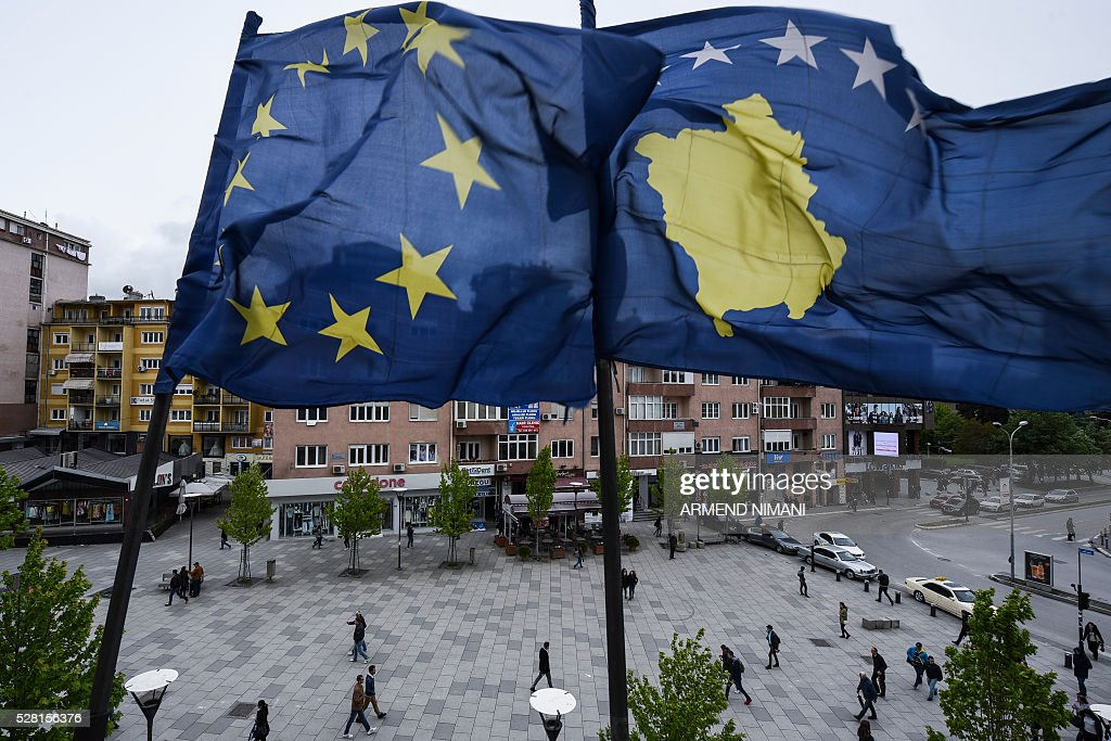 Kosovar Albanians walk under the EU and Kosovo flags in the main square of Pristina on May 4, 2016. The European Commission has proposed to lift visa requirements for citizens of Kosovo for short-term travel to the EU's passport-free Schengen zone. / AFP / ARMEND