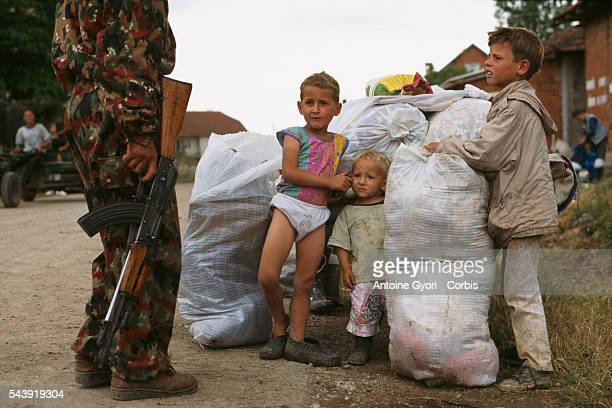 A Kosovar guerrilla fighting in the Yugoslavian Civil War stands next to a group of young boys and their sacks of belongings In the 1990s the...