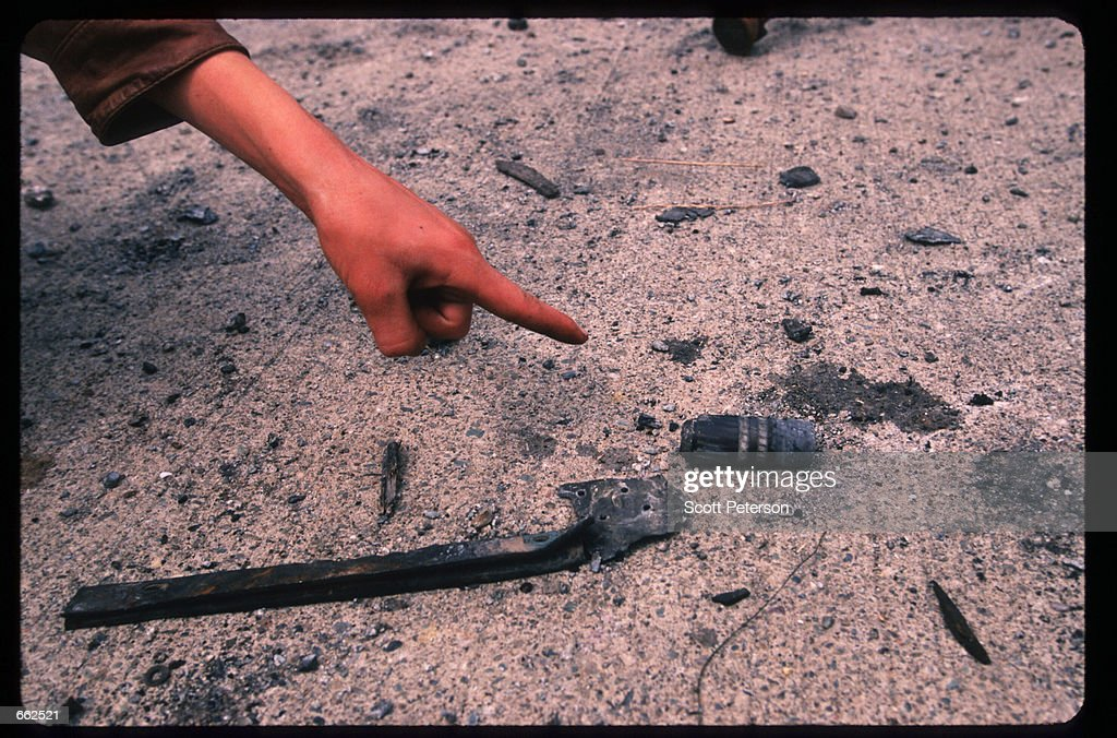 Kosovar points to a shell casing containing radiocative contaminated waste August 281999 Djakovica Kosovo Yugoslavia The western side of Djakovica is...