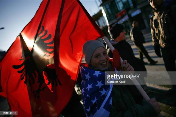 Kosovo Albanian child wearing a usamerican flag waves the albanian flag on the day their prime minister proclaimed Kosovo 'an independent sovereign...