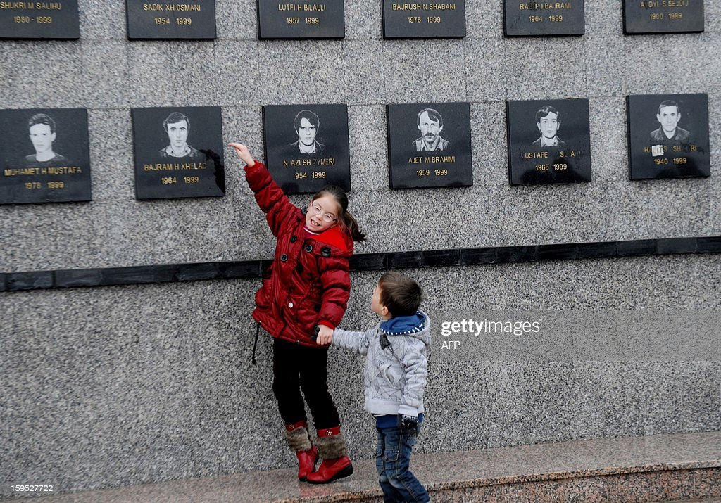 Kosovo Albanian children stand in front of commemorative plates in memories of victims of the Recak massacre on January 15, 2013. In 1999, forty-five Albanian civilians were killed by Serb forces, in the village of Recak. The massacre, one of the bloodiest that occurred in the Kosovo crisis, led to massive international pressure on Serbia to stop their ethnically motivated killings of civilian Albanians and to a NATO led air campaign that ousted Serbian security forces from Kosovo. AFP PHOTO/ARMEND NIMANI