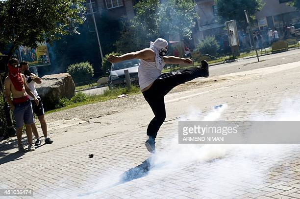 A Kosovo Albanian kicks back a tear gas grenade initially fired by antiriot police during clashes on June 22 2014 in the divided town of Mitrovica...