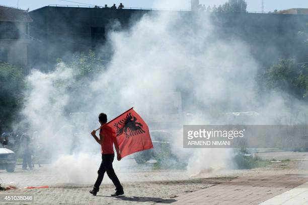 A Kosovo Albanian man holding an Albanian flag walks near tear gas fired by riotpolice during clashes on June 22 2014 in the divided town of...