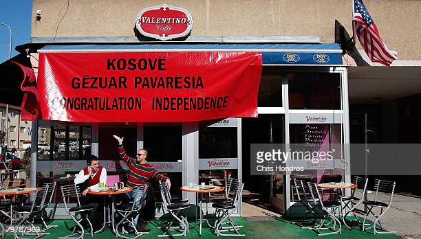 Kosovo Albanian man waves to a friend while another talks on a mobile phone under a banner celebrating upcoming independence February 15 2008 in...