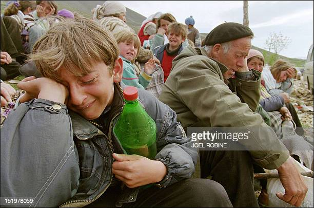 Kosovo Albanian refugees cry 15 April 1999 at the border between Yugoslavia and Albania near the northern town of Kukes Some 6600 Kosovo Albanian...