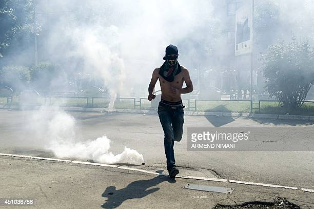 A Kosovo Albanian runs away from tear gas grenades fired by riot police during clashes on June 22 2014 in the divided town of Mitrovica Kosovo police...