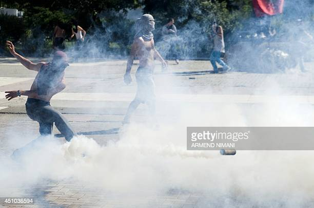 A Kosovo Albanian throws back a tear gas grenade initially fired by antiriot police during clashes on June 22 2014 in the divided town of Mitrovica...