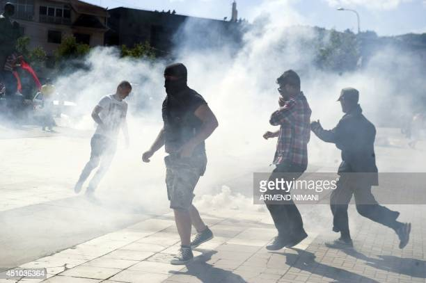 Kosovo Albanians run away from tear gas grenades fired by antiriot police during clashes on June 22 2014 in the divided town of Mitrovica Kosovo...