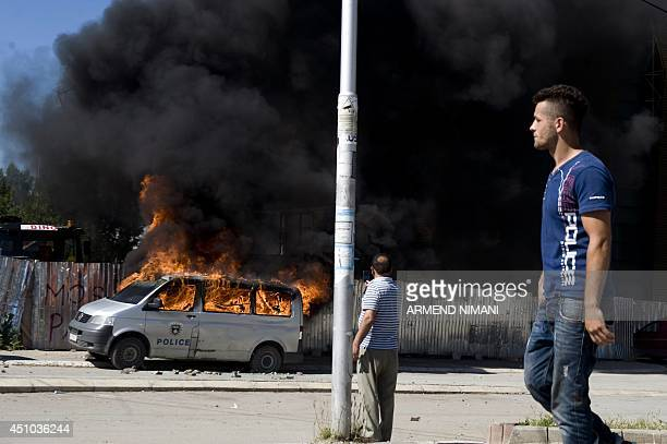 Kosovo Albanians walk past a burning police van during clashes between protesters and antiriot police on June 22 2014 in the divided town of...