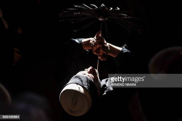 Kosovo dervish adept of Sufism a mystical form of Islam pierces his neck with a needle during a ceremony in a prayer room in Prizren on March 22 2017...