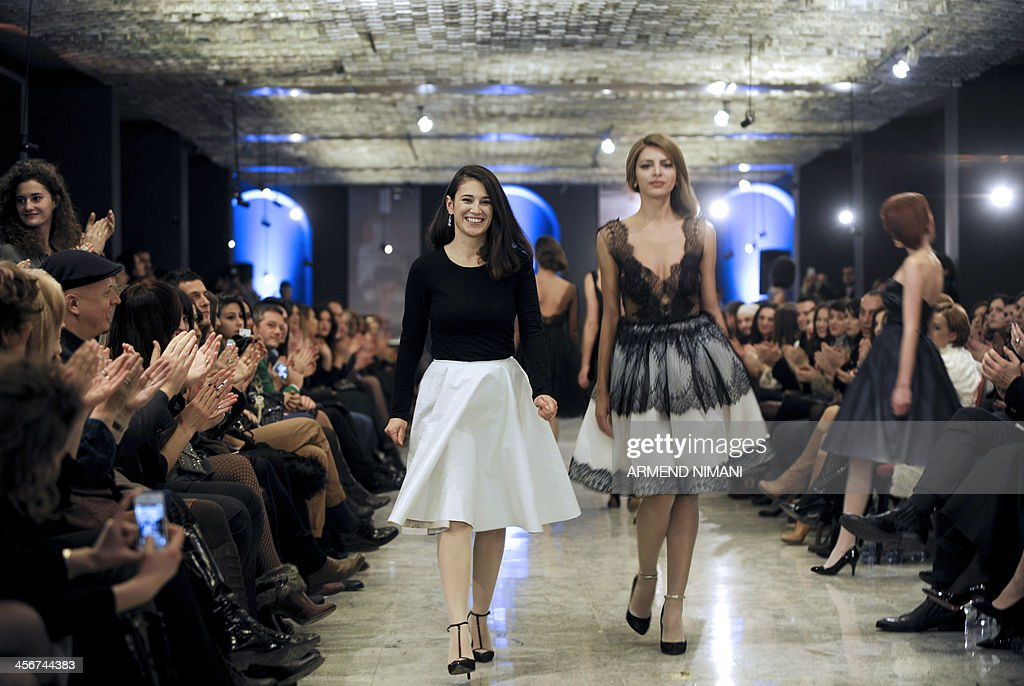 Kosovo Fashion designer Krenare Rugova (L) stands next to a model during the presentation of her spring/summer collection 'Cinematique' during a fashion show in Pristina on December 14, 2013.