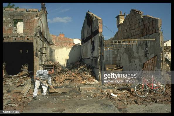 A Kosovo man cleans up the rubble from houses destroyed during the Yugoslavian Civil War In the 1990s the Serbiancontrolled government attempted to...
