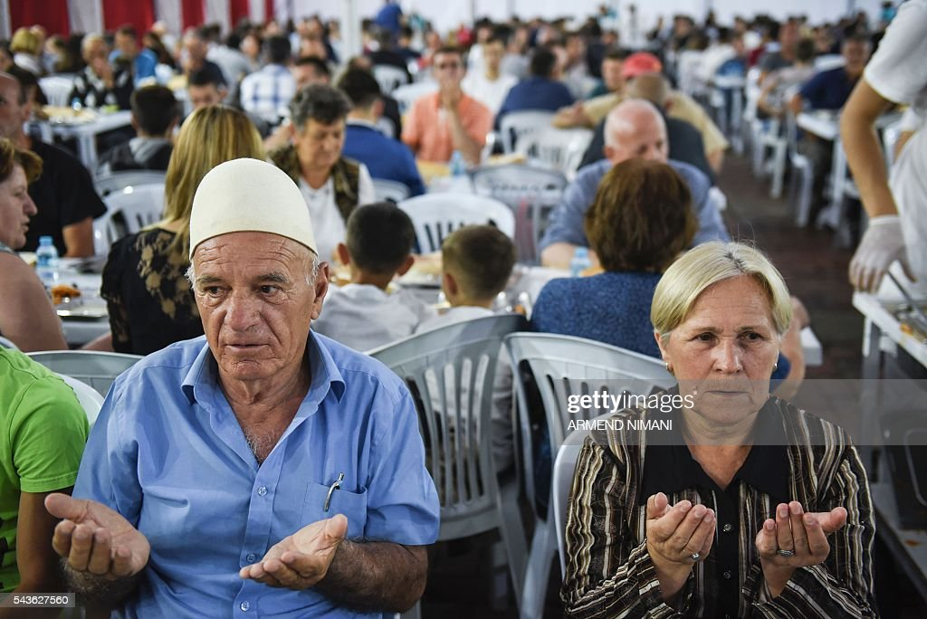 A Kosovo muslim couple pray before breaking the fast with a dinner distributed for free during the Muslim fasting month of Ramadan on June 29, 2016 in Pristina. Muslims fasting in the month of Ramadan must abstain from food, drink and sex from down to dusk, when they break the fast with meal known as iftar. / AFP / ARMEND