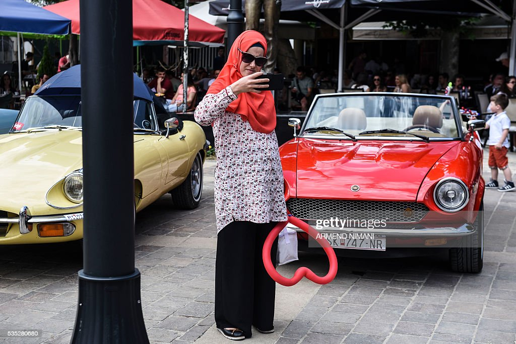 A Kosovo Muslim woman makes a selfie in front of vintage cars displayed during the 11th Old Timers Fest on May 29, 2016 in Prizren. / AFP / ARMEND