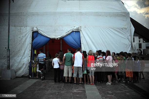 Kosovo Muslims wait in line outside a tent to break the fast with a diner distributed for free during the Muslim fasting month of Ramadan on July 30...