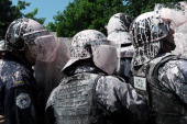Kosovo Police splashed with paint clash with demonstrators in Pristina on June 27 2013 during a protest against the ratification of the agreement...