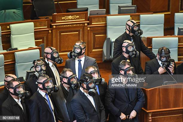 TOPSHOT Kosovo police wearing gas masks stand guard after the Parliament opposition lawmakers released tear gas in the Kosovo's parliament in...