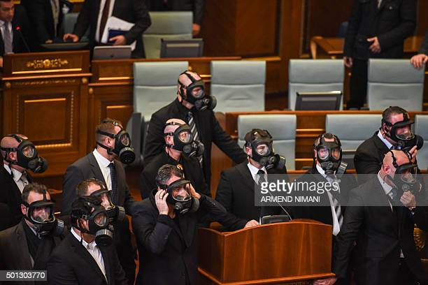 Kosovo police wearing gas masks stand guard after the Parliament opposition lawmakers released tear gas in the Kosovo's parliament in Pristina on...