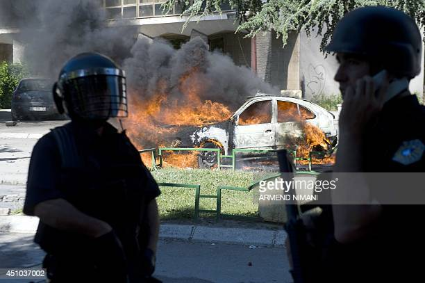 Kosovo riotpolice officers stand near a burning car during clashes with protesters on June 22 2014 in the divided town of Mitrovica Kosovo police...