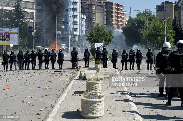 Kosovo riotpolice stand in line during clashes with protesters on June 22 2014 in the divided town of Mitrovica Kosovo police used tear gas today to...