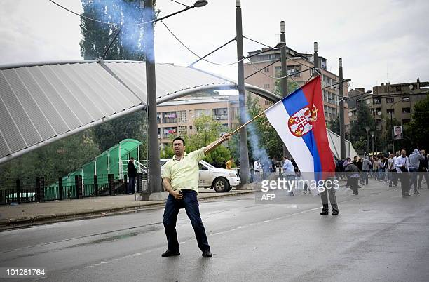 A Kosovo Serb waves a Serbian flag during a protest in the divided town of Mitrovica on May 30 2010NATO peacekeepers and Kosovo riot police Sunday...