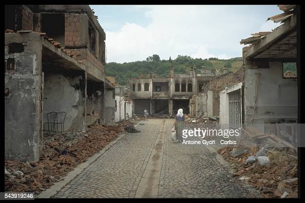 A Kosovo woman walks through her town its buildings destroyed during the Yugoslavian Civil War In the 1990s the Serbiancontrolled government...