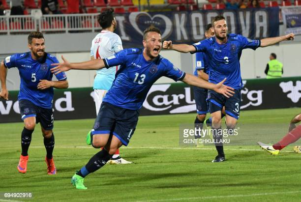 Kosovo's Amir Rrahmani celebrates with teammates Enis Alushi and Fidan Aliti after scoring during the FIFA World Cup 2018 qualification football...