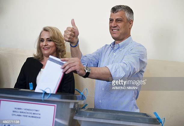 Kosovo's Prime minister Hashim Thaci gestures as he casts his ballot next to his wife Lumnije at a polling station in Pristina on June 8 during...