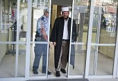 Kosovo's top radical cleric the imam of the Grand Mosque in Pristina Shefqet Krasniqi is escorted by a Kosovo police officer as he leaves the court...