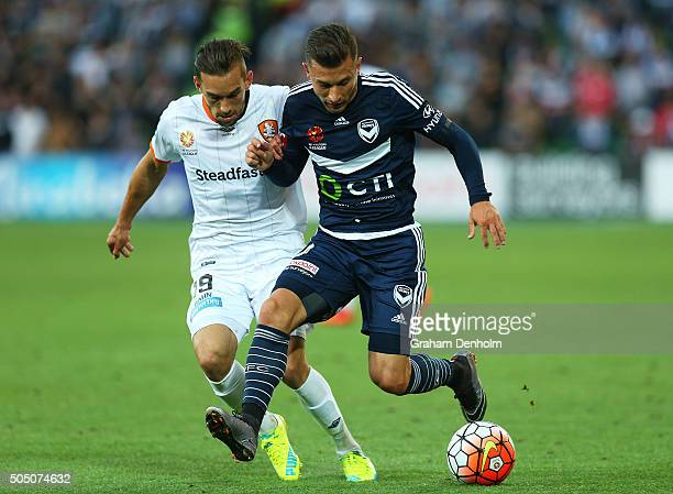 Kosta Barbarouses of Melbourne Victory and Jack Hingert of Brisbane Roar compete for the ball during the round 15 ALeague match Melbourne Victory and...