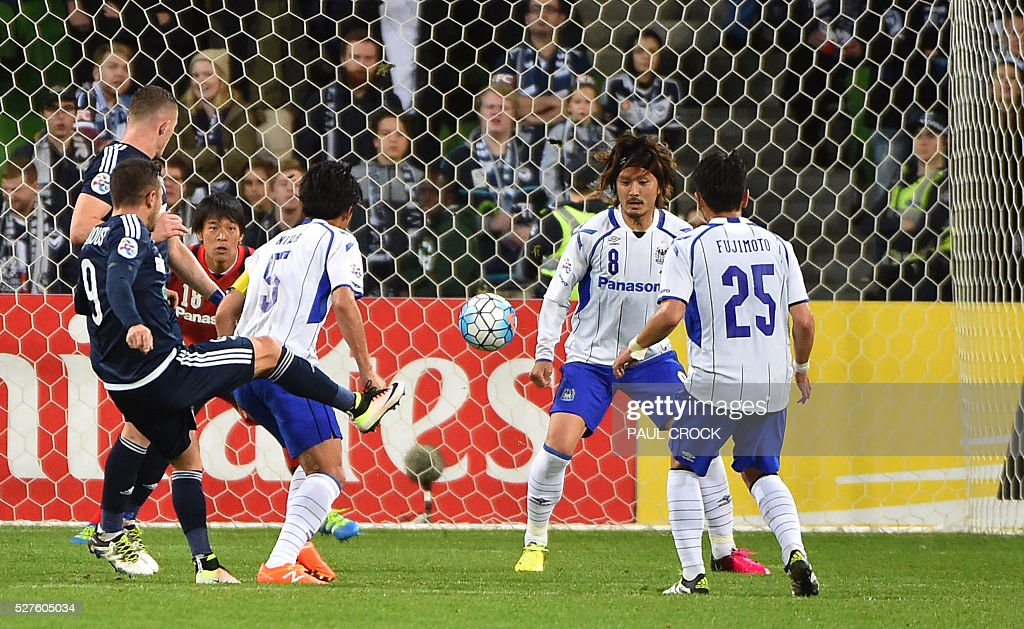 Kosta Barbarouses (L) of Melbourne Victory fires the ball through Gamba Osaka defenders during the AFC Champions League football match between Melbourne Victory and Gamba Osaka in Melbourne on May 3, 2016. / AFP / Paul Crock / IMAGE