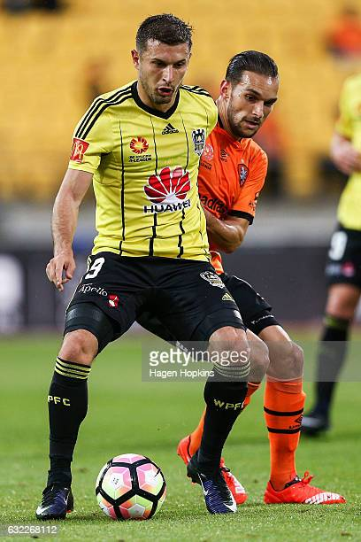 Kosta Barbarouses of the Phoenix holds off the challenge of Jack Hingert of the Roar during the round 16 ALeague match between the Wellington Phoenix...