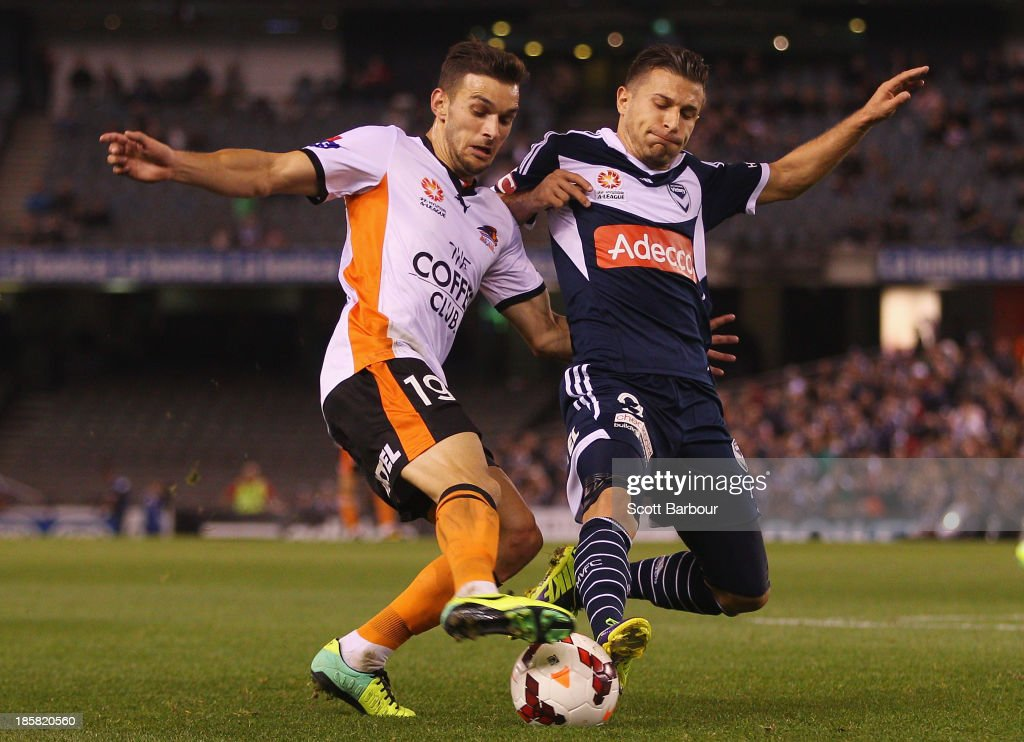Kosta Barbarouses of the Victory and Jack Hingert of the Roar compete for the ball during the round three A-League match between Melbourne Victory and Brisbane Roar at Etihad Stadium on October 25, 2013 in Melbourne, Australia.