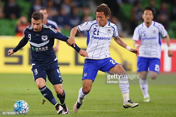 Kosta Barbarouses of the Victory and Yosuke Ideguchi of Gamba Osaka compete for the ball during the AFC Champions League match between Melbourne...