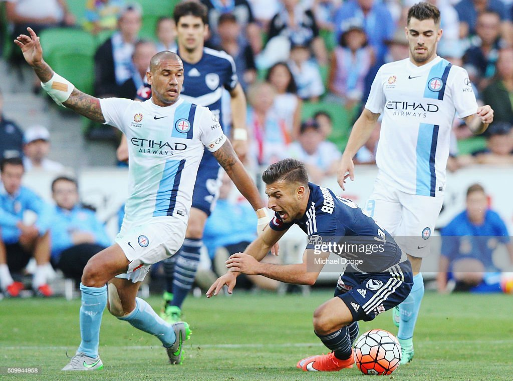 Kosta Barbarouses of the Victory stumbles in his contest for the ball against Patrick Kisnorbo of the City during the round 19 A-League match between Melbourne City FC and Melbourne Victory at AAMI Park on February 13, 2016 in Melbourne, Australia.