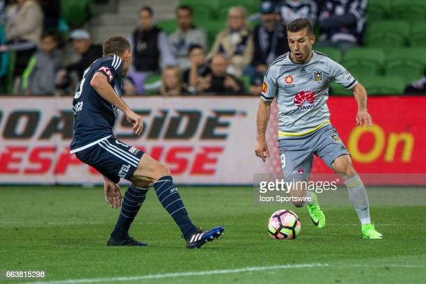 Kosta Barbarouses of the Wellington Phoenix controls the ball in front of Alan Baro of Melbourne Victory during the round 25 match of the Hyundai...