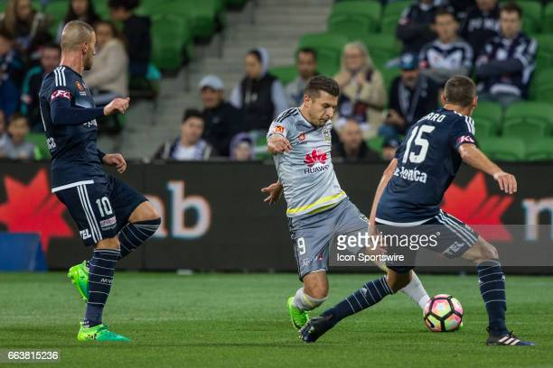 Kosta Barbarouses of the Wellington Phoenix kicks the ball across goal in front of James Troisi of Melbourne Victory and Alan Baro of Melbourne...