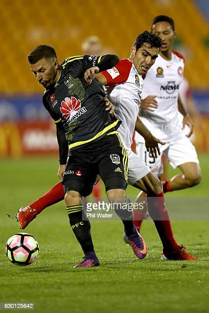 Kosta Barbarrouses of Wellington is tackled by Jaushua Sotirio of Western Sydney during the round 11 ALeague match between Wellington and Western...