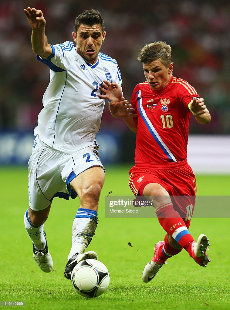Kostas Katsouranis of Greece and Andrey Arshavin of Russia battle for the ball during the UEFA EURO 2012 group A match between Greece and Russia at The National Stadium on June 16, 2012 in Warsaw, Poland.