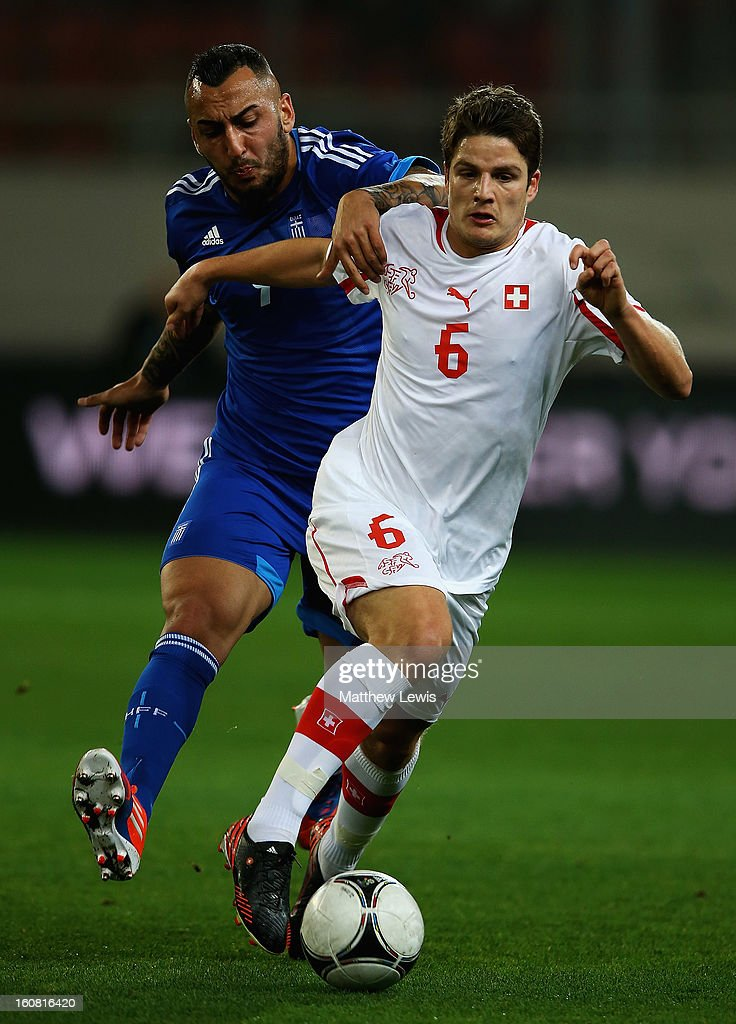 Kostas Mitroglou of Greece and <a gi-track='captionPersonalityLinkClicked' href=/galleries/search?phrase=Pirmin+Schwegler&family=editorial&specificpeople=604263 ng-click='$event.stopPropagation()'>Pirmin Schwegler</a> of Switzerland challenge for the ball during the International Friendly match between Greece and Switzerland at Karaiskakis Stadium on February 6, 2013 in Athens, Greece.