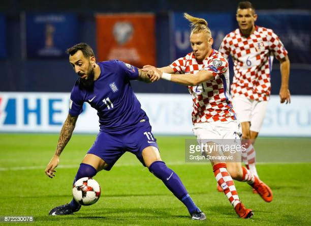 Kostas Mitroglou of Greece is challenged by Domagoj Vida of Croatia during the FIFA 2018 World Cup Qualifier PlayOff First Leg between Croatia and...