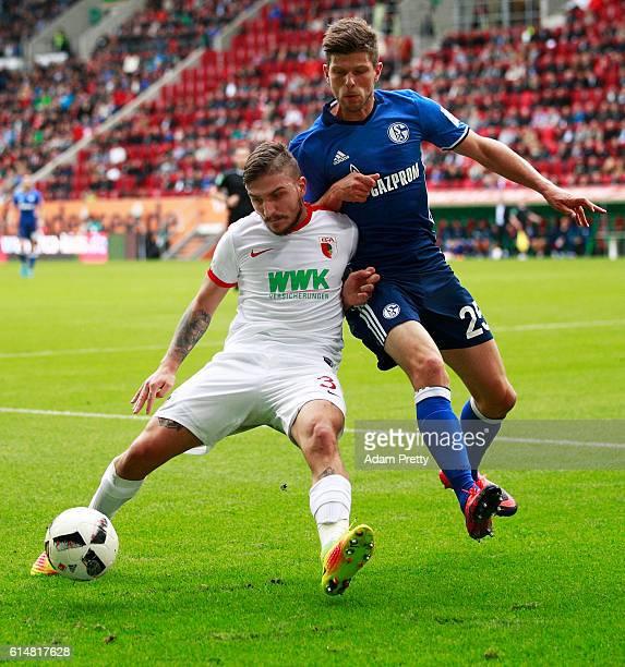 Kostas Stafylidis of Augsburg challenges KlassJan Huntelaar of Schalke 04 during the Bundesliga match between FC Augsburg and FC Schalke 04 at WWK...